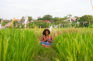 young beautiful and happy black afro American woman sitting at rive field outdoors practicing yoga relaxation and meditation enjoying holidays