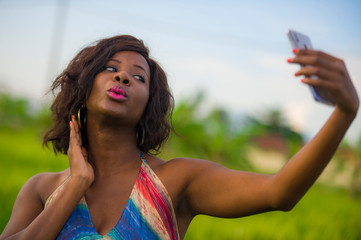 happy and attractive black African American woman in beautiful dress taking selfie portrait with internet mobile phone enjoying holidays travel in Asia  smiling cheerful at rice field