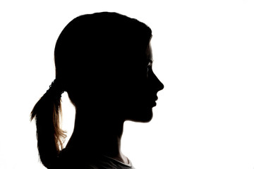 Dark silhouette profile of a young girl on a white background, concept of anonymity
