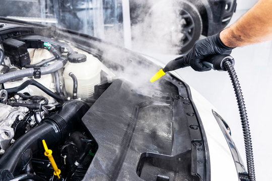 Car detailing. Car washing cleaning engine. Cleaning car using hot steam. Hot Steam engine washing. Soft lighting. Car washman worker cleaning vehicle.