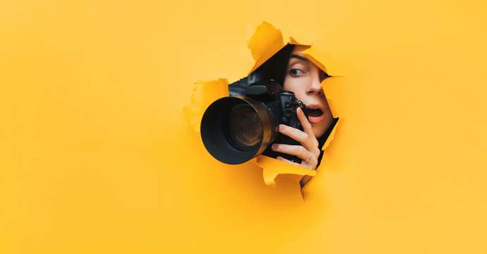 A paparazzi girl with a camera looks out from cover and looks at what is happening with her mouth open. Yellow paper, torn hole. Tabloid press. Copy space.