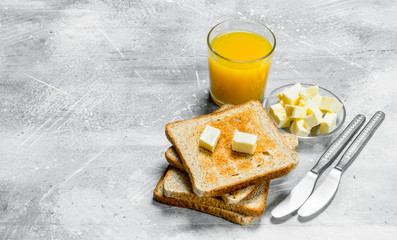 Breakfast. Toasted bread with butter and a glass of orange juice.