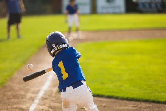 Youth baseball player hitting ball