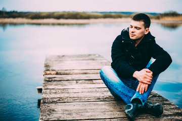 Young handsome man sitting on wooden pier, relaxing,  thinking, listening. Casual style - jeans, jacket