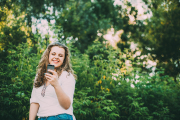 Young Beautiful Pretty Plus Size Caucasian Girl Woman Dressed In White Blouse And Blue Jeans Enjoying Life, Smiling And Using Smartphone Standing In Summer Green Forest Woods Bushes
