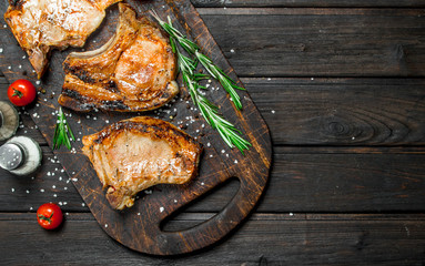 Grilled pork steaks with rosemary and fresh tomatoes.