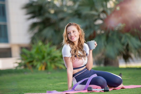 Beautiful Caucasian woman with long brown hair sitting on a yoga mat in the park drinking a cup of tea or coffee and smiling