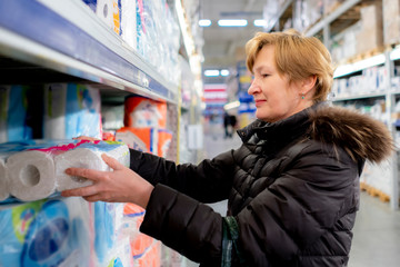 woman chooses toilet paper in the store