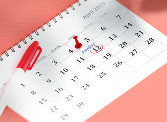 Concept image of calendar with blue pin and gold coins. 3D Render Illustration isometric calendar of 12 april payday or payroll. Pinned day, closeup.