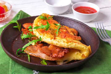 Delicious bacon omelette with arugula and colorful pickled tomatoes.Close up