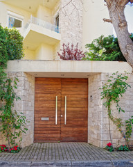 elegant contemporary house entrance wooden door and red flowers, Athens Greece
