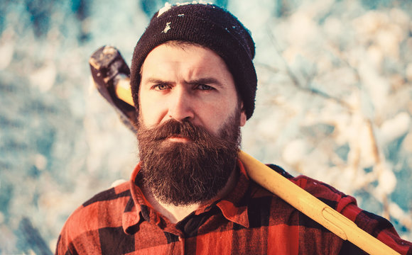 Bearded lumberjack. Male holds an ax on a shoulder. Brutal bearded man. Brutal bearded lumberjack with ax in winter forest. Lumberjack with an ax in his hands. Handsome man, hipster in snowy forest.
