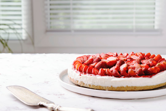 Strawberry cheesecake on white table near window. Selective focus