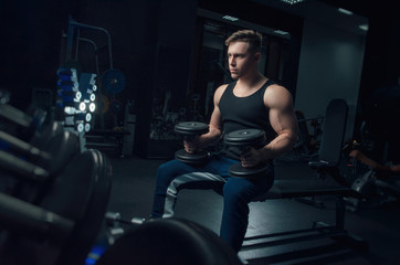 the sporty boy trains with dumbbells