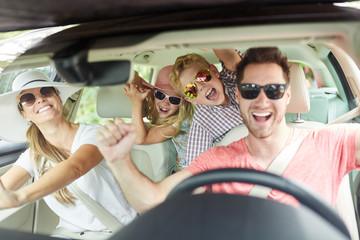 Familie mit Sonnenbrille singt im Auto Wall mural