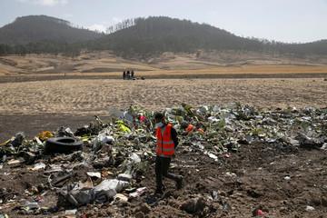 Man walks past debris of the Ethiopian Airlines Flight ET 302 plane crash, near the town of Bishoftu, near Addis Ababa
