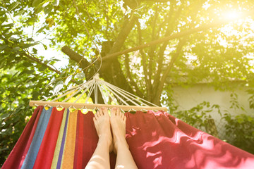 Fit girl is lying in the colourful hammock. Woman with beautiful legs is relaxing in hippie style garden near the village house. Rustic holidays concept.