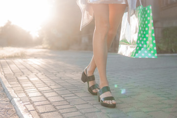 Shopping day concept. CLose-up of young woman carrying shopping bags while walking along the street during sunset backlight