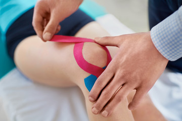 Kinesiology. Therapist taping knee with physio tape