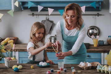 Mother and daughter coloring eggs at home