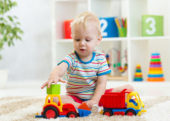 Nursery baby boy playing with toy cars in kindergarten