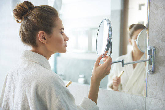Lady looking at small round vanity glass mirror