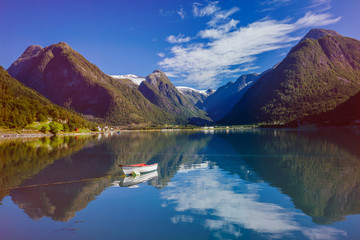 Amazing nature view with boat, fjord and mountains. Beautiful reflection. Norway.