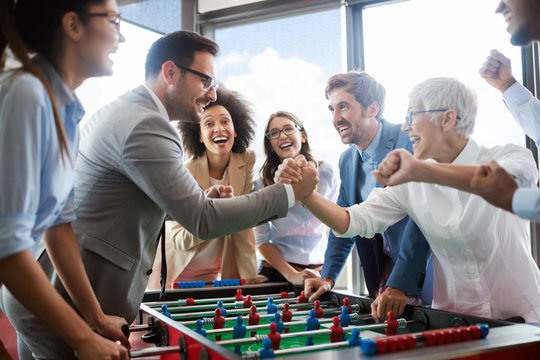 Business people having great time together.Colleagues playing table football in office.