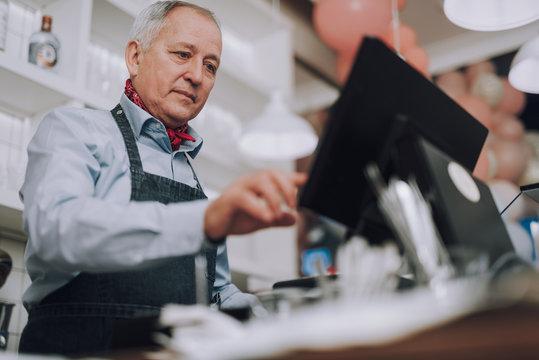 Senior man in denim apron working with digital cash register