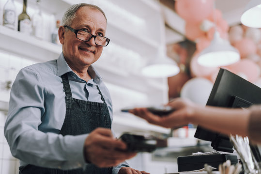 Friendly shop owner in glasses accepting payment from customer