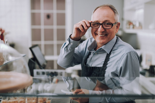 Good-looking gentleman in glasses sitting behind the counter in shop