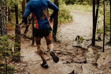 Fototapete - back dirty man runner running on stones forest trail marathon