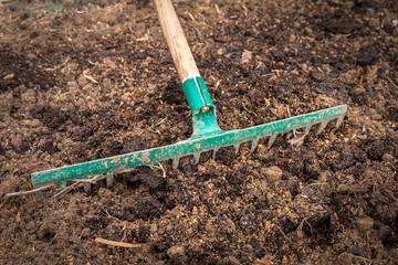 Worker with rake preparing soil for planting - gardening concept