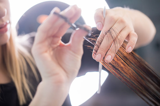 Close up of clean hair with scissors in arms of stylist