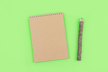 Eco natural mockup with craft recycled paper notepad and pen in the form of a tree trunk with bark on green background. Spring minimal pastel background