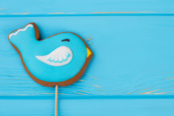Bird cookie decorated with frosting. Biscuit in a shape of bird on color background with copy space. Traditional pastry for Easter holiday.