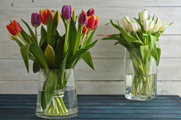 Bouquet of colorful tulips in a glass vase on a wooden background. A bouquet of white tulips in the background