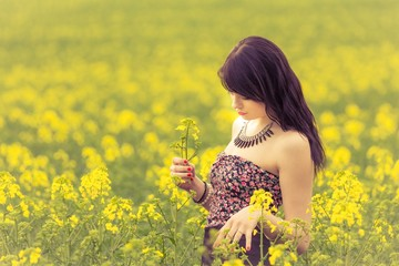 Beautiful woman in sunny summer love looking at rapeseed flower. Attractive young beauty girl enjoying the warm sunny sun in nature rapeseed field takes time feeling sustainability and contemplation
