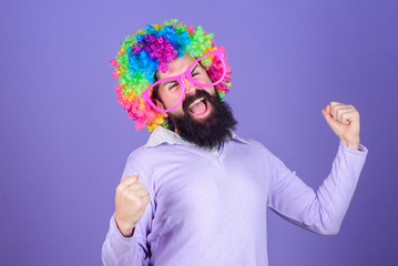 Having fun. Holiday fun and carnival concept. Man bearded wear colorful wig and funny glasses on violet background. Clown and circus. Party fun. Enjoy being crazy. Feel free to express yourself