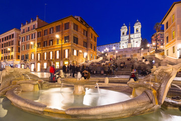 Fountain on the Piazza di Spagna square and the Spanish Steps in Rome at night, Italy