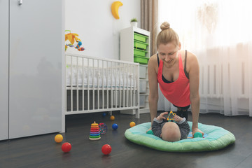 young woman doing push ups at home while playing with her little baby