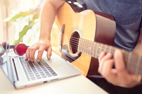 Musician playing acoustic guitar and recording music on computer