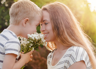 A small son gives his mother a bouquet of delicate flowers. Love, the concept of family recreation. Women's Day. mothers Day