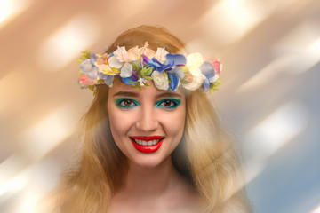 Studio shot of a young smiling woman  with makeup and floral wreath on her head