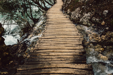 Wooden pathway on streaming water in Plitvice National Park, Croatia, Europe. Popular nature tourist attraction Plitvice lakes.
