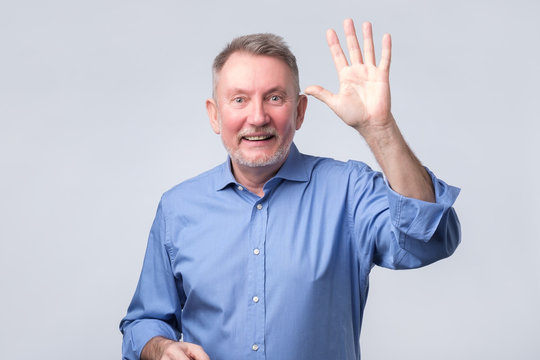 Portrait of a mature man in blue shirt wave hand welcome.