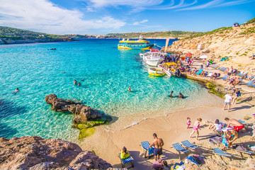 Obraz Comino, Malta - November, 2018: Tourists crowd at Blue Lagoon to enjoy the clear turquoise water on a sunny summer day with clear blue sky and boats on Comino island, Malta. - fototapety do salonu