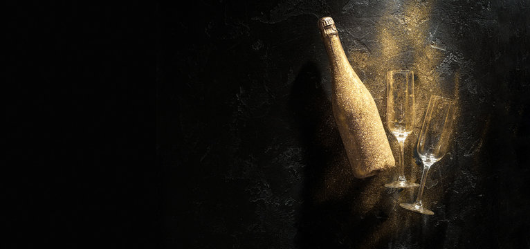 Photo of golden champagne bottle, two wine glasses on black stone background