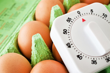 Egg timer and brown eggs in egg box