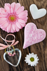 Pink flowers and hearts against wooden background